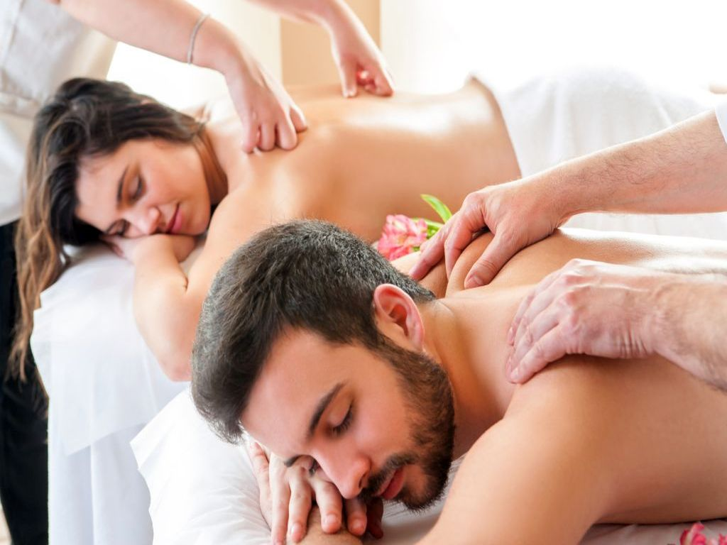 Couple having relaxing body massage in spa.Two therapists doing back massage on couple at the same time.